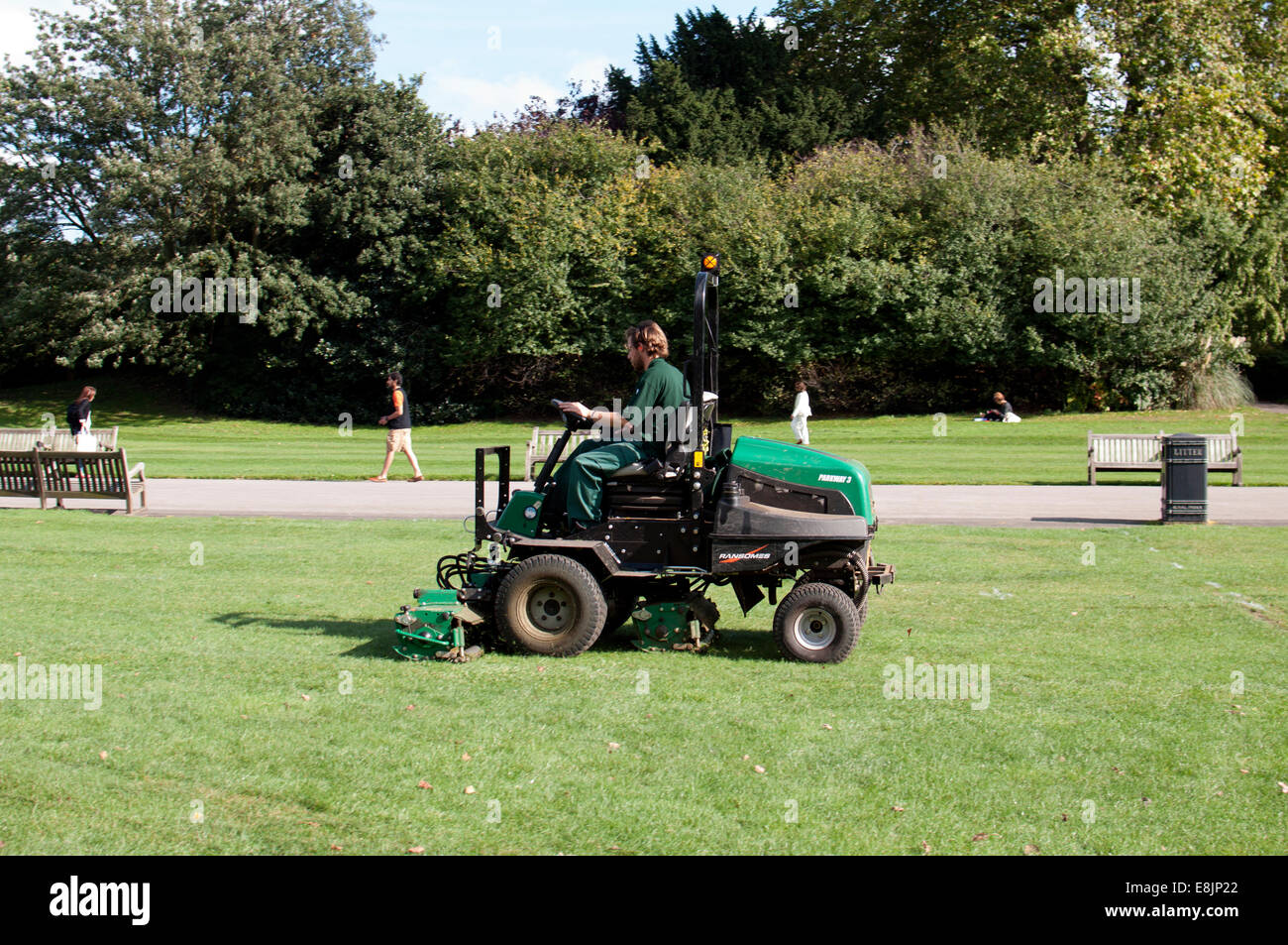 Gardener mowing lawn in Regents Park, London, UK - Stock Image