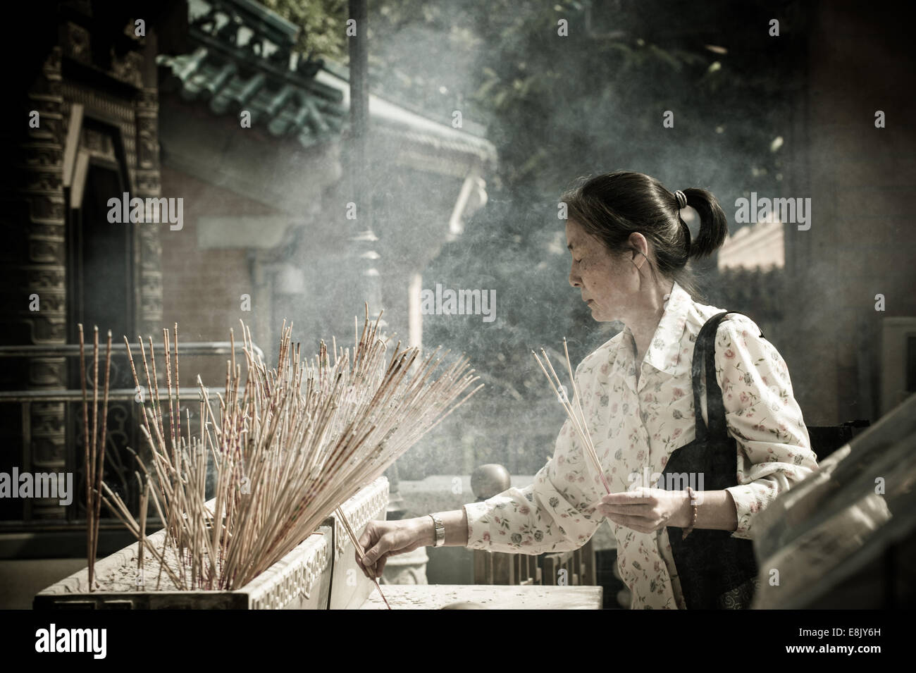 Worshiper holding burning joss sticks during a celebrations in Wong Tai Sin temple, Kowloon. Hong Kong, China - Stock Image