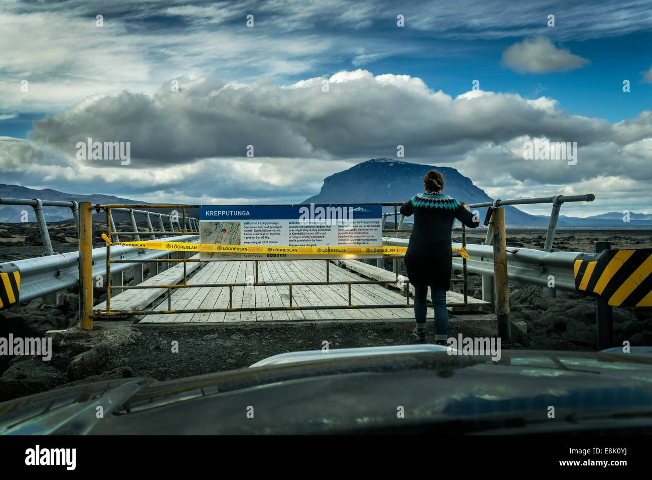 Woman standing by a closed bridge-Krepputunga area, by the Holuhraun Fissure Eruption, near the Bardarbunga Volcano, - Stock Image
