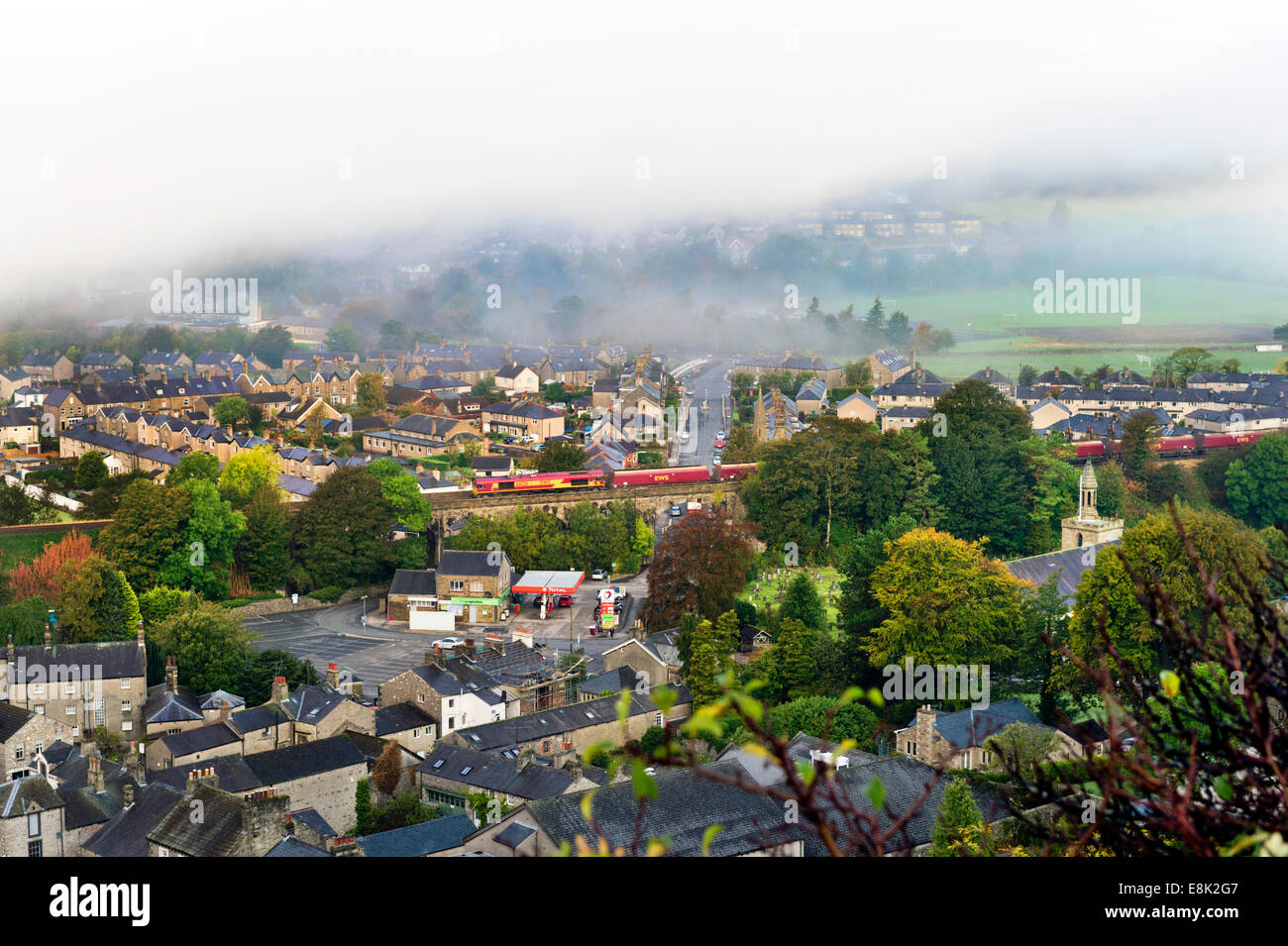 Misty Autumn morning, with low cloud, over Settle, North Yorkshire, UK, with freight train crossing bridge. - Stock Image
