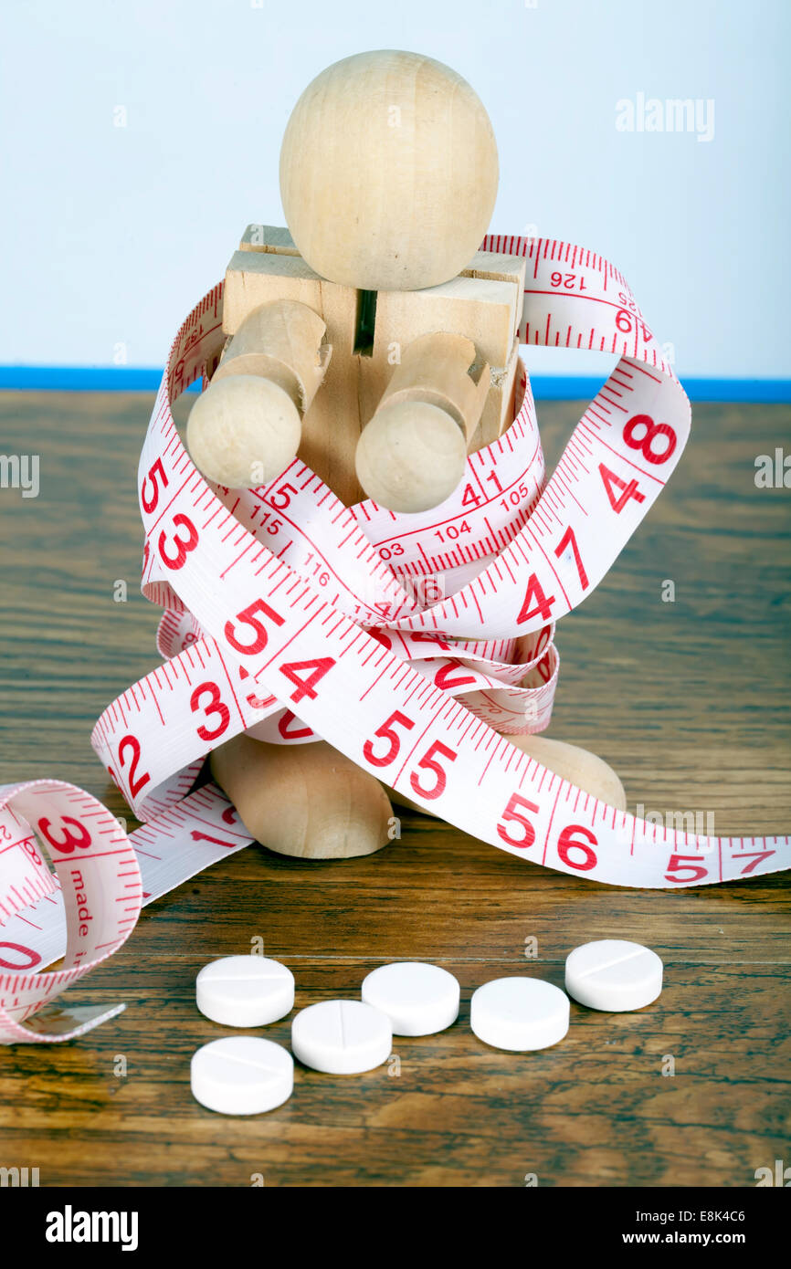 Weight loss concept with wooden man wrapped in measuring tape and diet pills - Stock Image