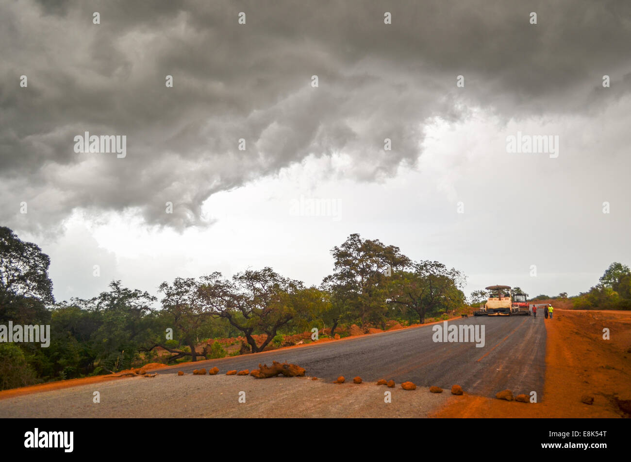 Road construction during the rainy season with threatening clouds, in the Fouta near Labé, Guinea, Africa - Stock Image