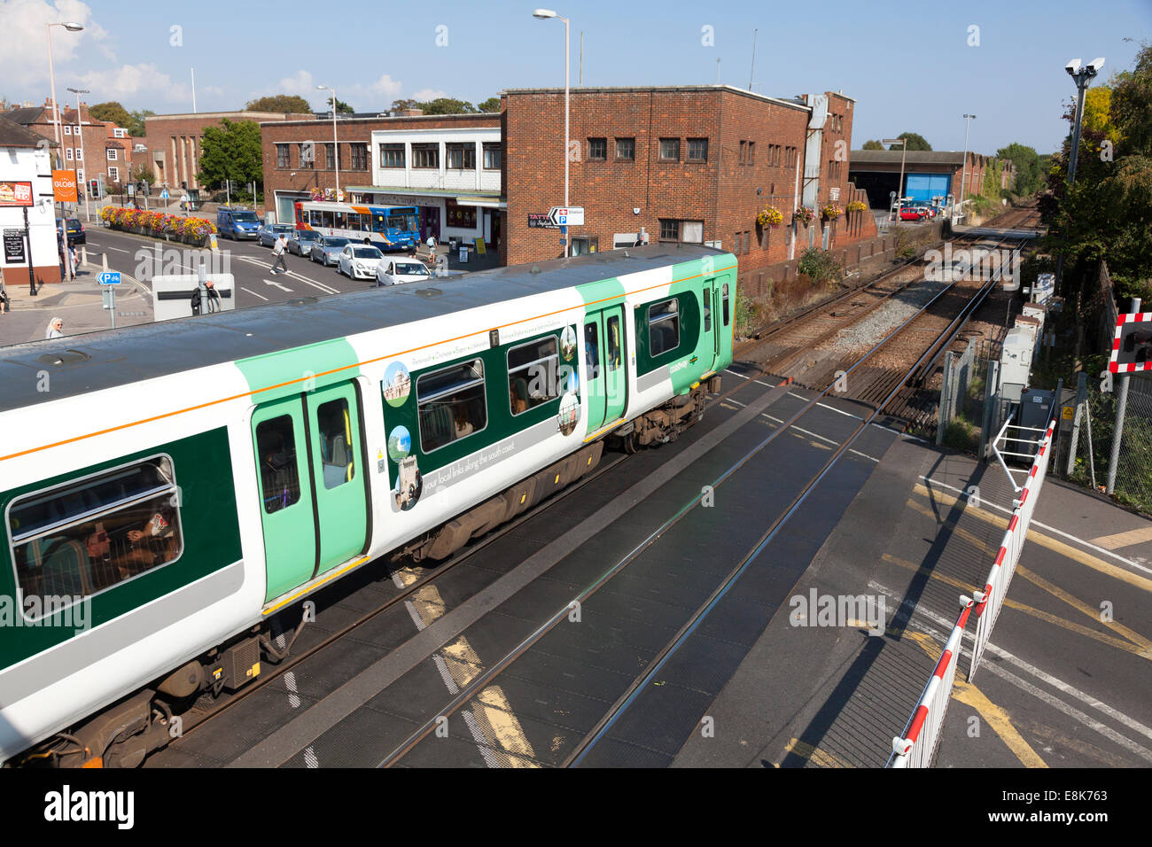 Southern Railway train passing over level crossing, Chichester, West Sussex Stock Photo