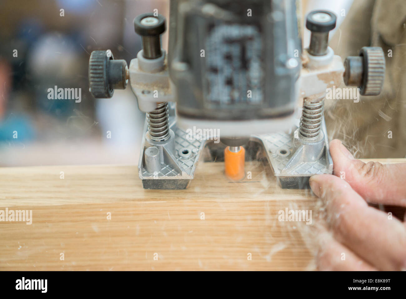 Blurred motion of carpenter working, preparing door for hinges - Stock Image