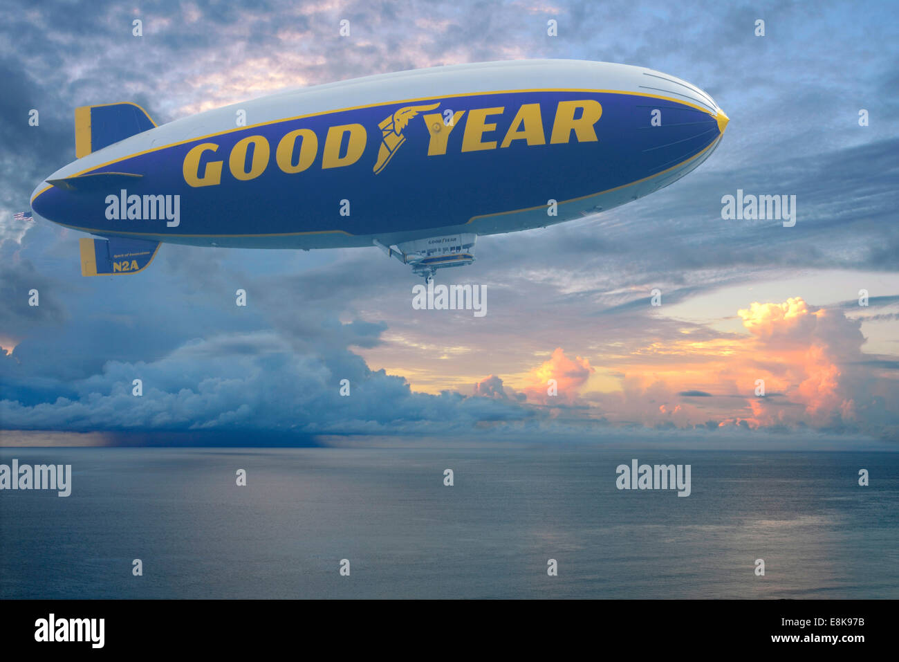 The Goodyear Blimp makes its way across the Atlantic shore just after sunrise as a thunderstorm builds on the horizon. - Stock Image