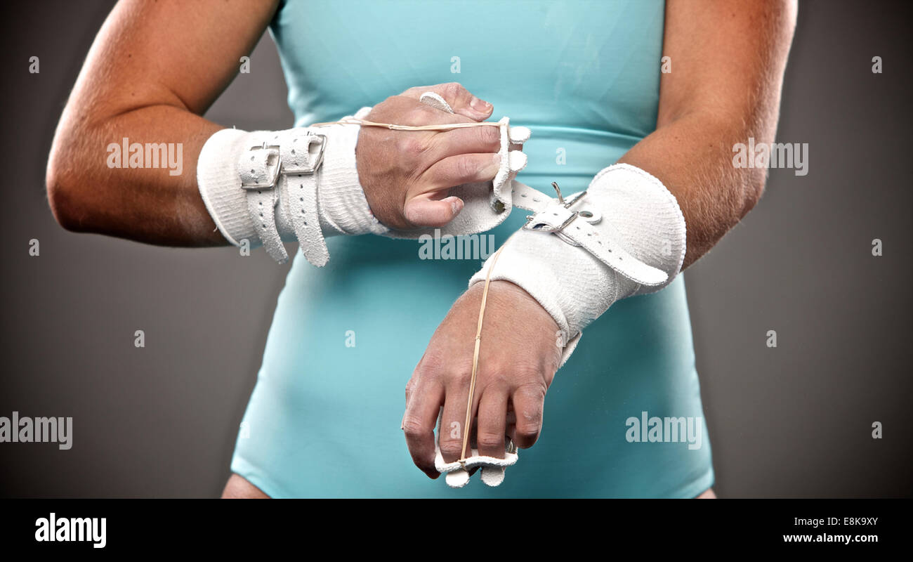young athletic fit woman putting on her grips to prepare for gymnastics uneven bars routine workout - Stock Image