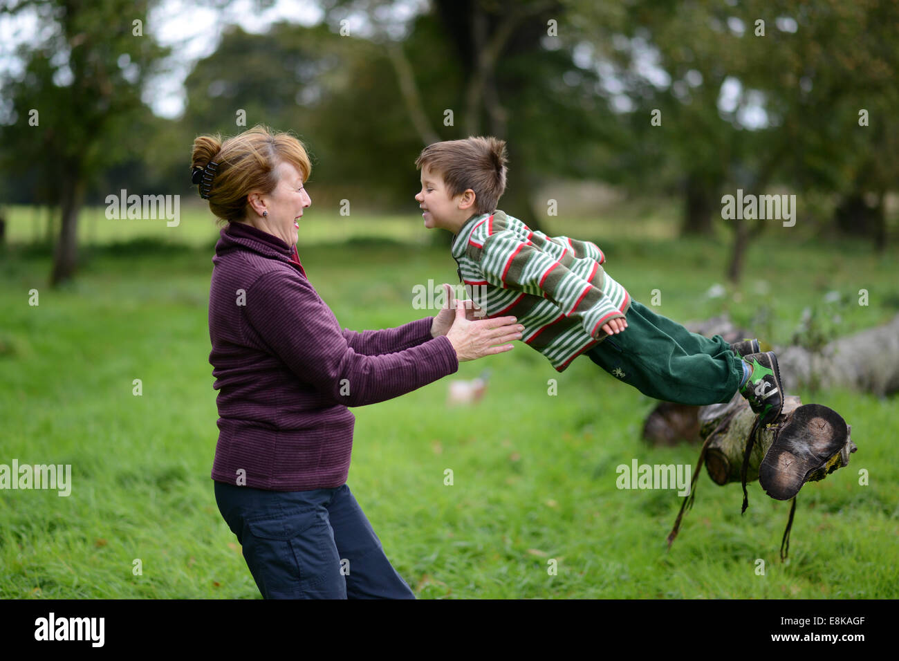 Child children boy having outdoor fun with grandmother jumping into the arms trust trusting Uk - Stock Image