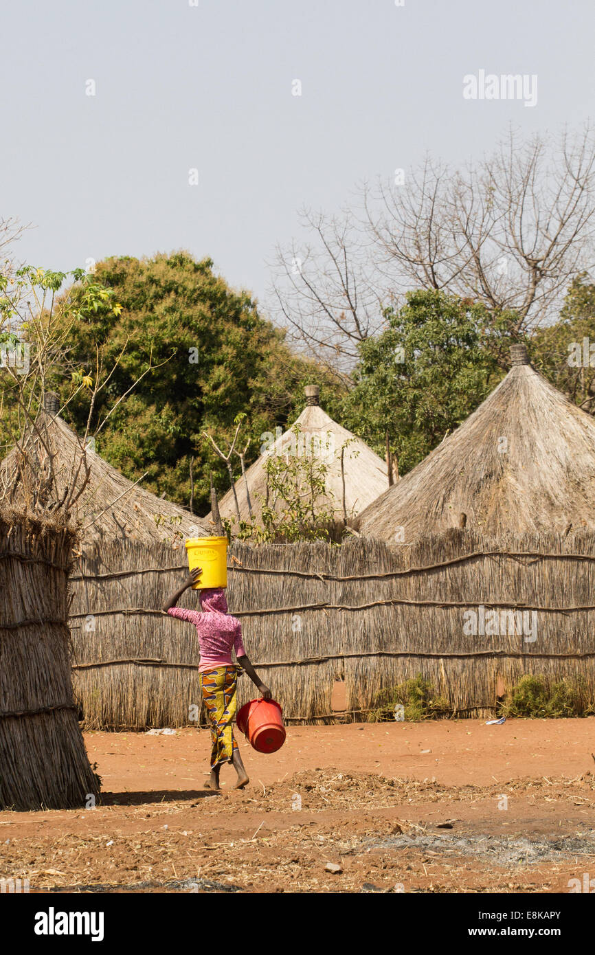 A Zambian / African woman in a typical traditional village carries water in a container on her head - Stock Image