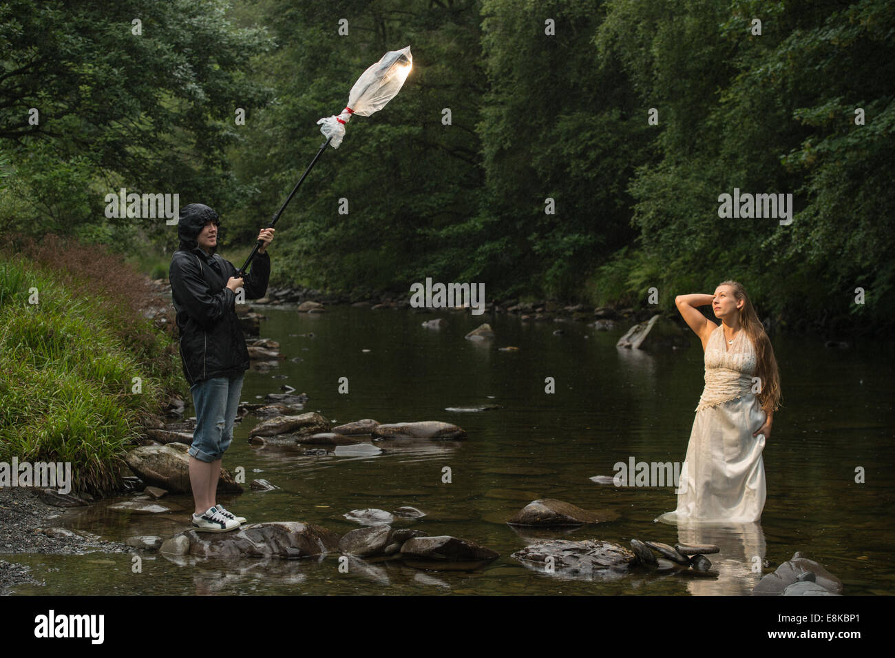 Trash the dress photo shoot : a 'bride' wearing her wedding dress standing in river - photographers assistant - Stock Image