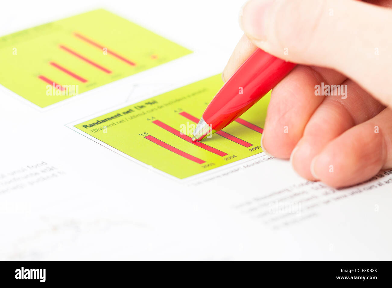 Close-up of female hand holding pen over business graph - Stock Image