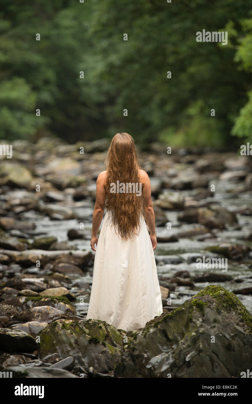 Trash the dress: rear view of a blonde haired 'bride' wearing her wedding dress stood standing in a riverbed - Stock Image