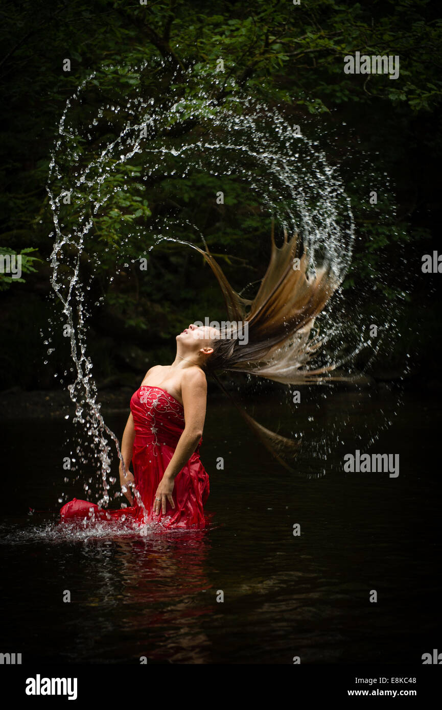 Fibonacci sequence: A blonde haired woman girl wearing a deep red frock ball gown in a river flicking flipping her - Stock Image