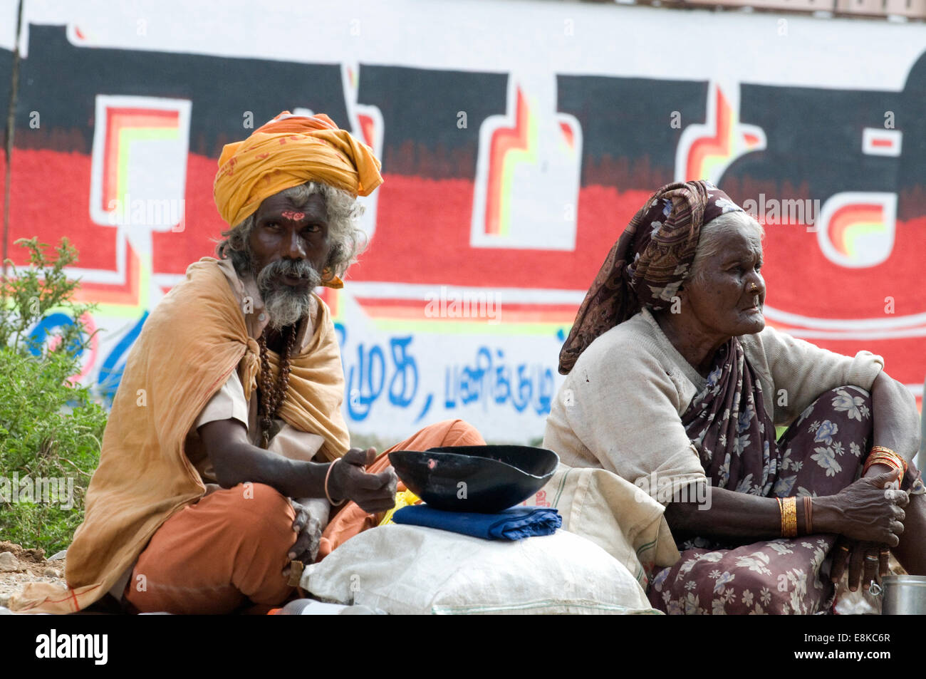 Sadhu in safron robes and turban sat with lady on the pradacshina street around Arunachala sacred mountain Tiruvannamalai Stock Photo