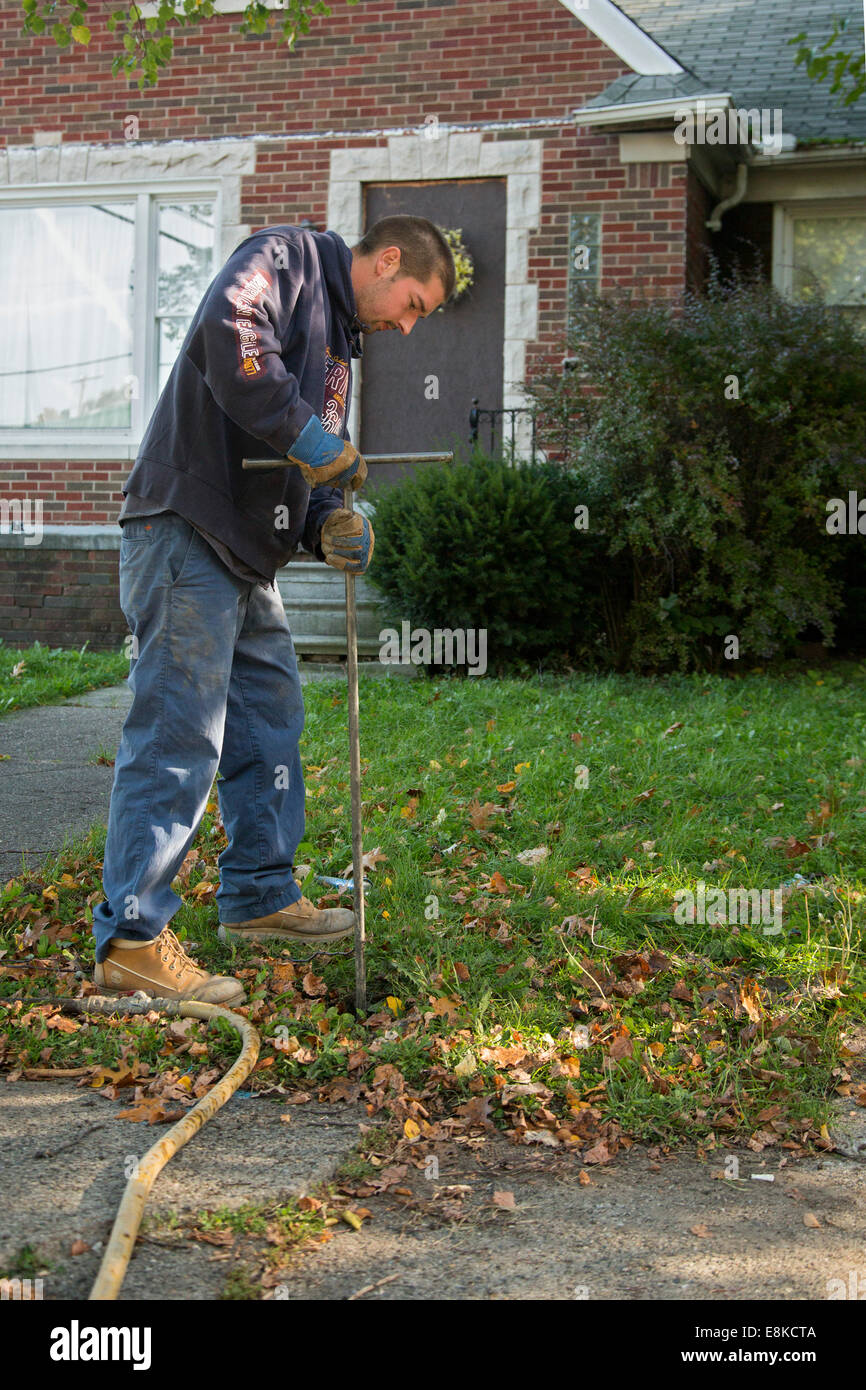 Detroit, Michigan - A worker for the city's contractor, Homrich, shuts off water service to a home in Detroit. - Stock Image