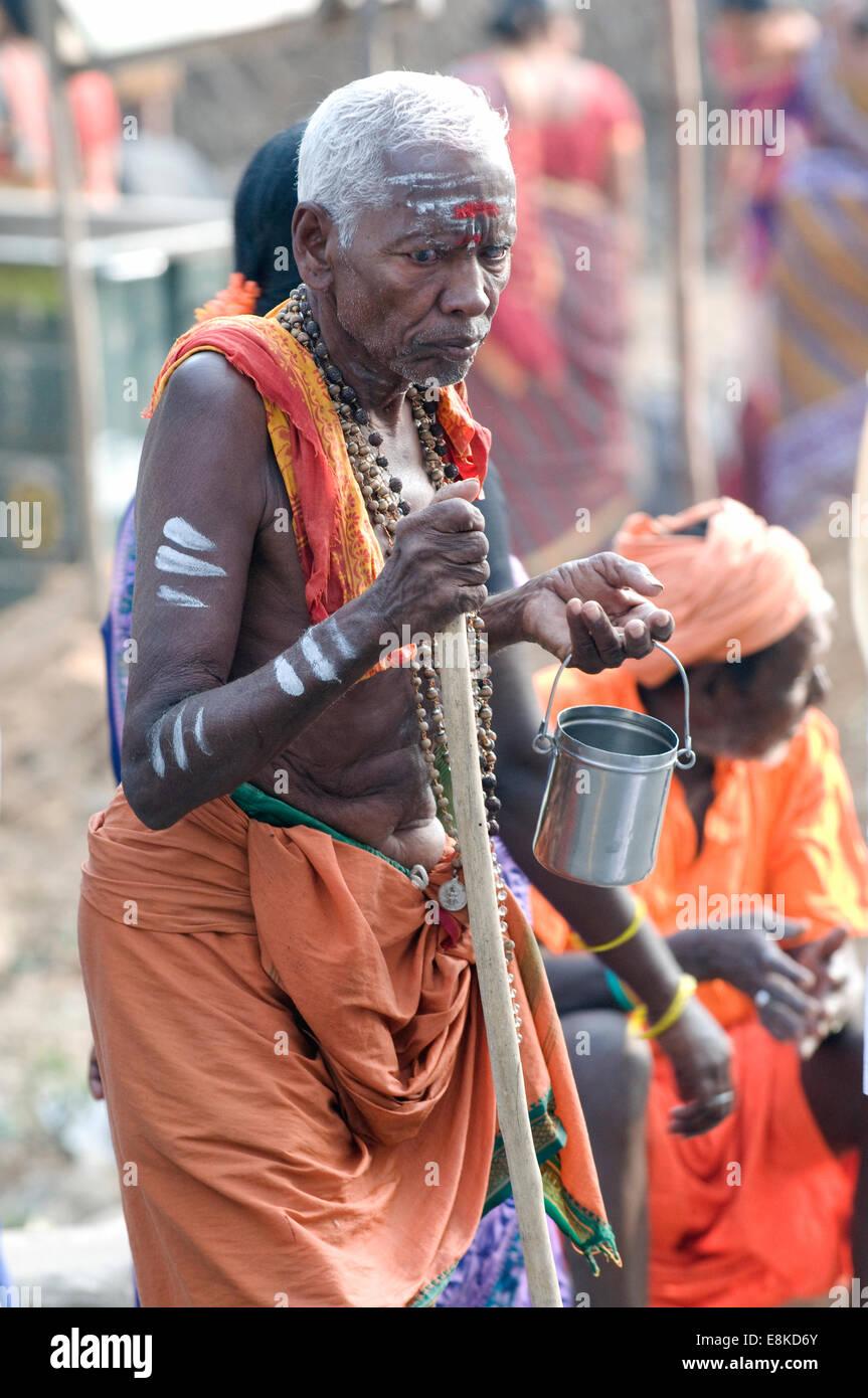 Old blind sadhu seeking alms in safron orange lungi outside Agni (fire) Lingam (Siva) Pradacshina shrine Arunachala Stock Photo