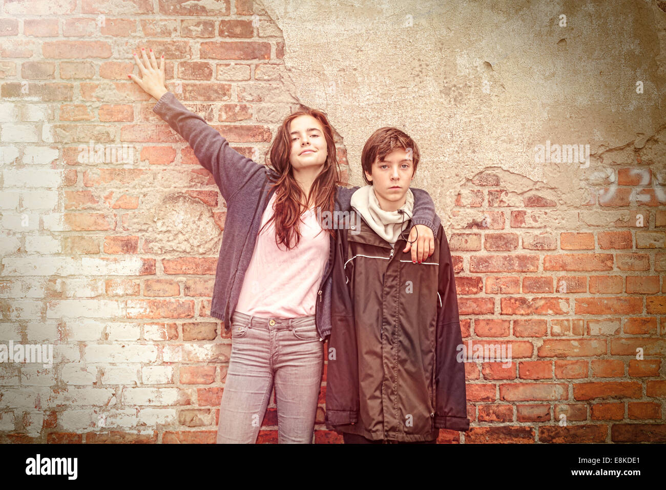 siblings in front of an old grungy brick wall - Stock Image