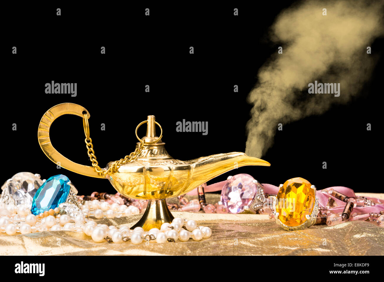 The formation of a magical deity from a gold, magic lamp surrounded by a wealth of jewelry and fantasy. - Stock Image