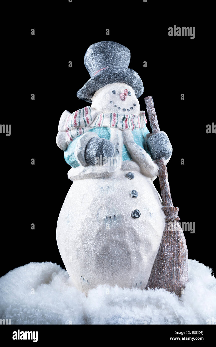 A decorative snowman in the dark, cold outdoors during the holiday season. - Stock Image