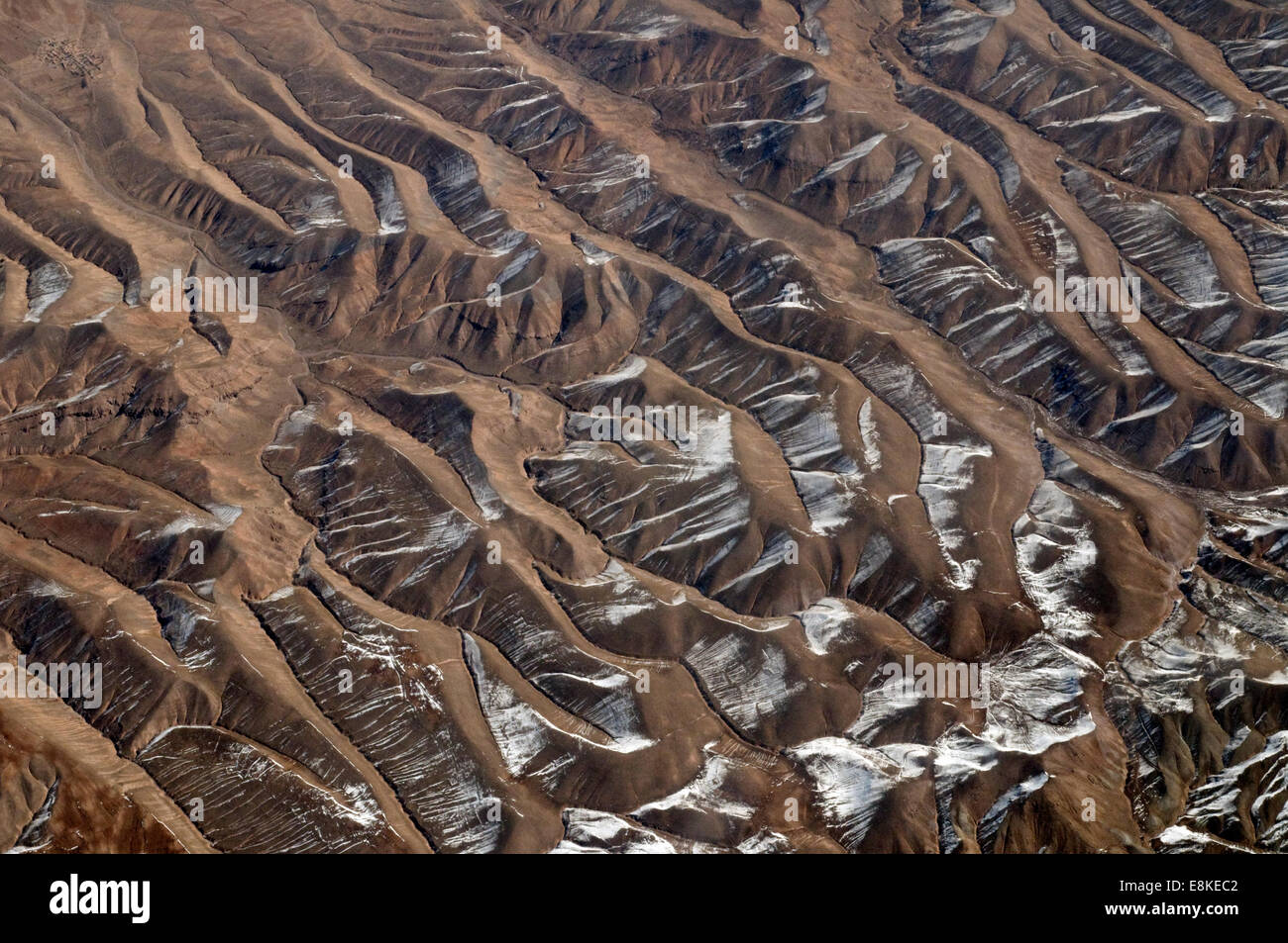 Aerial of mountainous snow clad rock formations in a barren Turkmenistan mountainous region. Snow clad rugged range - Stock Image