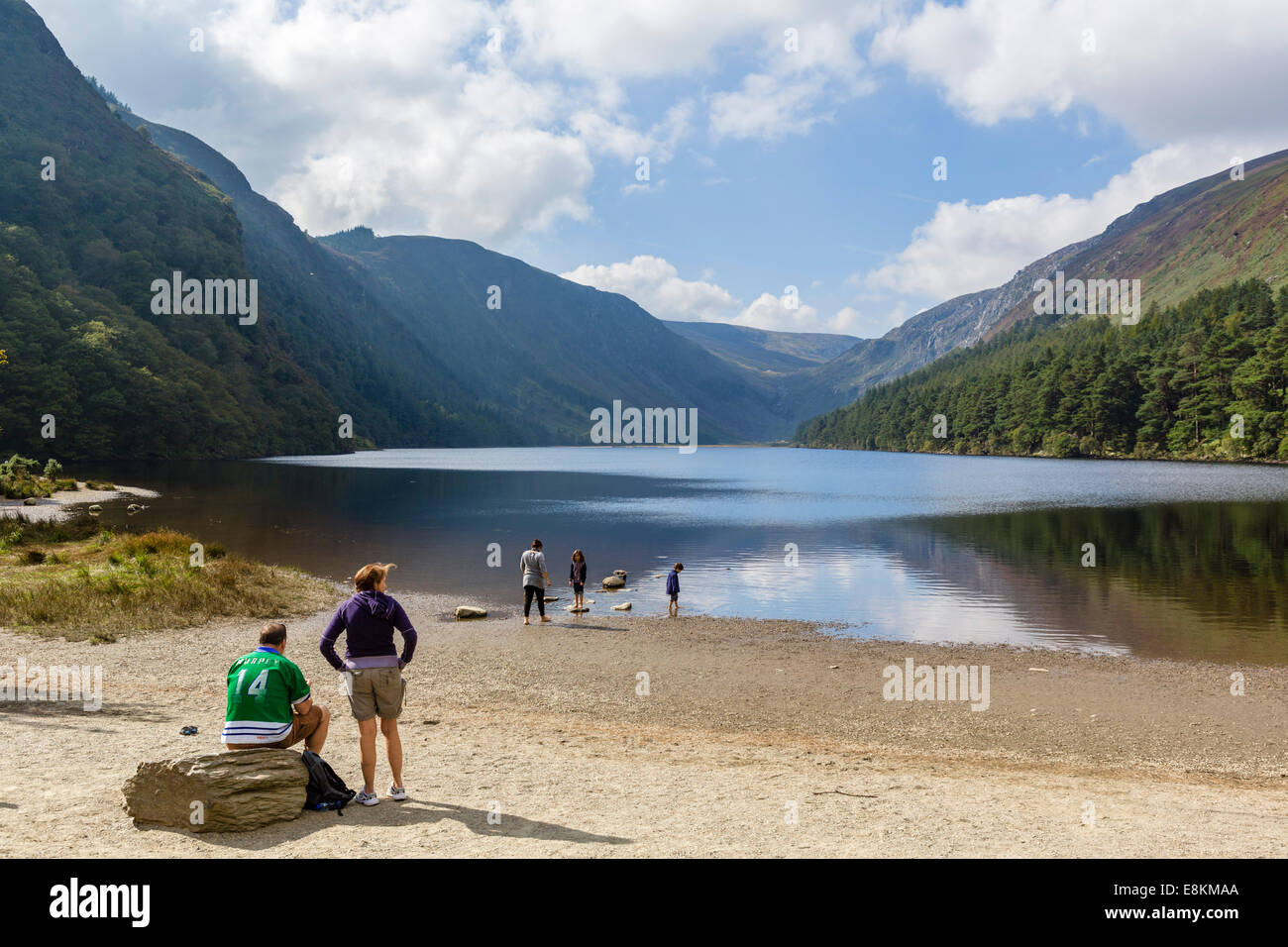 Family on the shores of the Upper Lake at the old monastic settlement of Glendalough, County Wicklow, Republic of - Stock Image