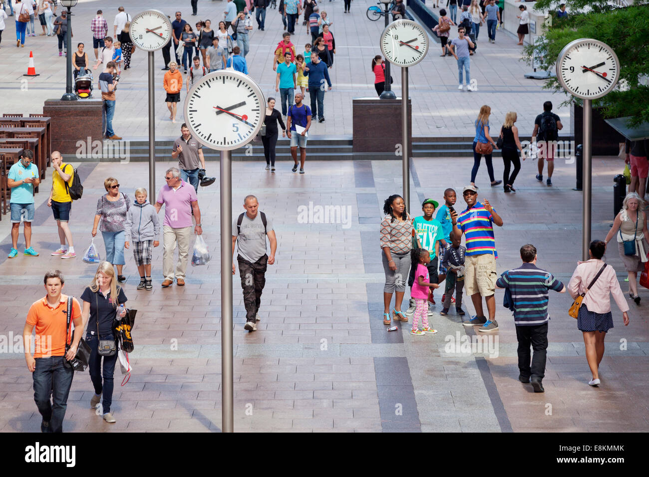 People in a square with clocks, Canary Wharf, Docklands, London, England, United Kingdom - Stock Image