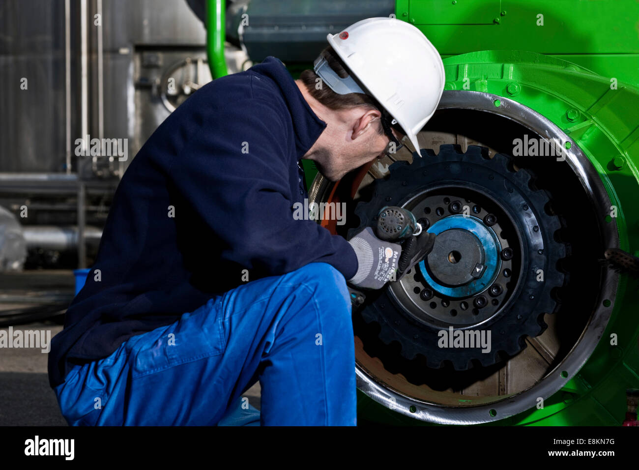Technician attaching the connecting gear-wheel of an electric generator with an impact wrench - Stock Image