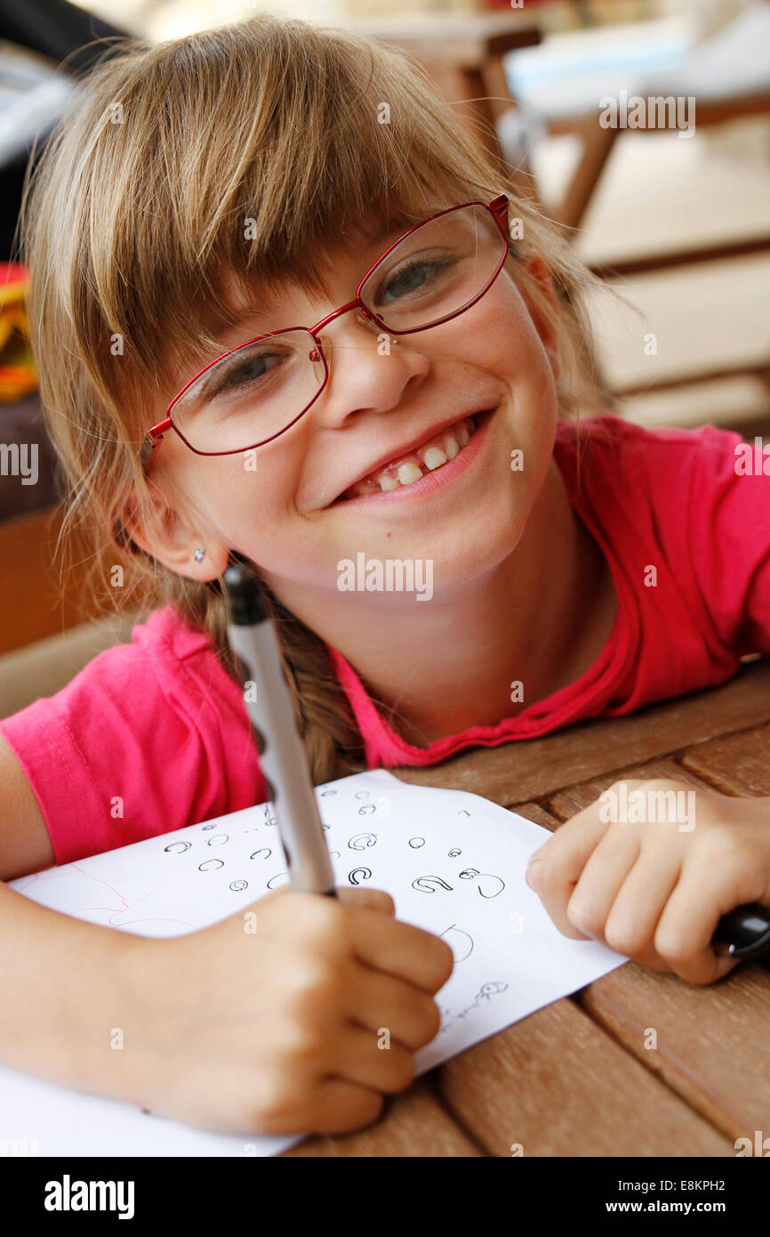 A 6-year old girl practising writing during the holidays. - Stock Image