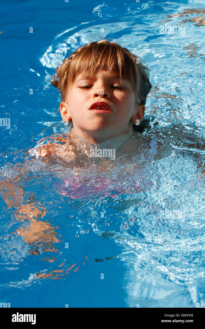 A 6-year old girl swimming for the first time without armbands in a swimming pool. Stock Photo