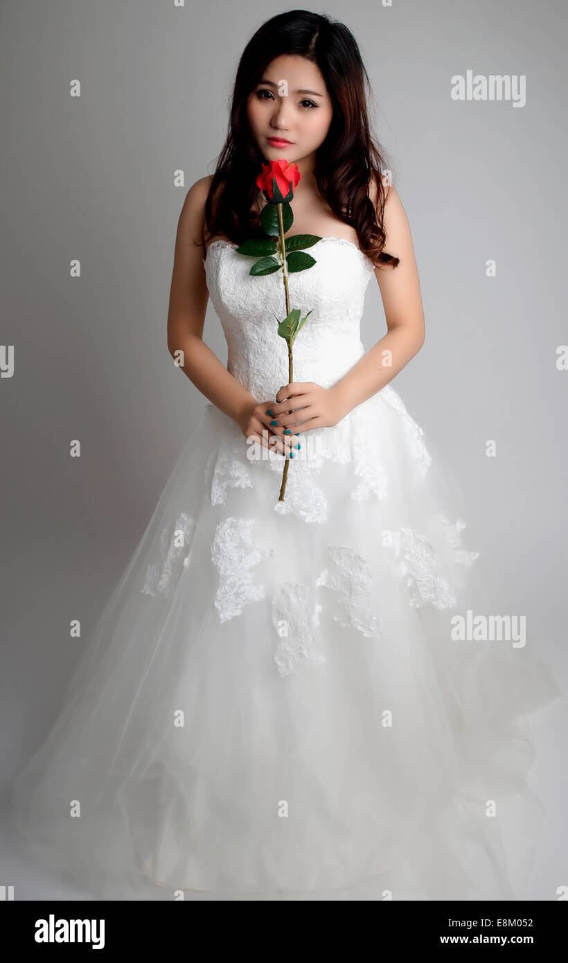 e25d8550f8fb Cute bride wearing a white wedding dress and holding a red rose ...