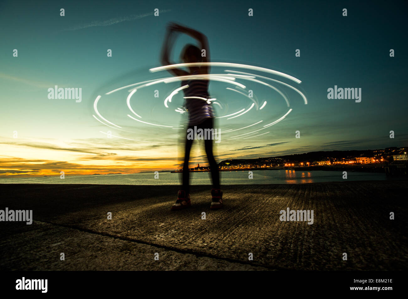 A woman in silhouette hula hooping with an illuminated hula hoop at dusk twilight - long exposure light trails circles - Stock Image