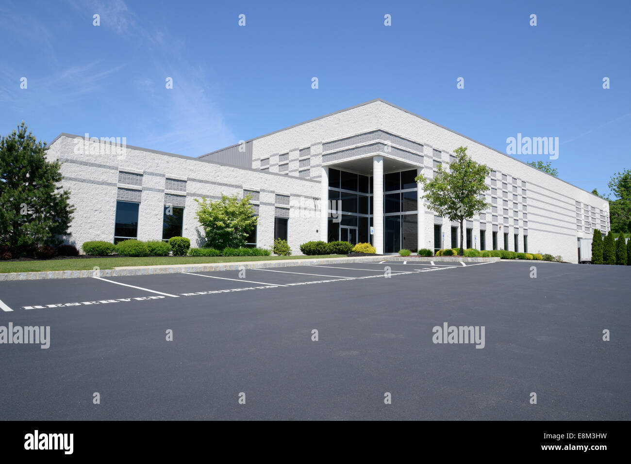 exterior of a large corporation building by an asphalt parking area - Stock Image