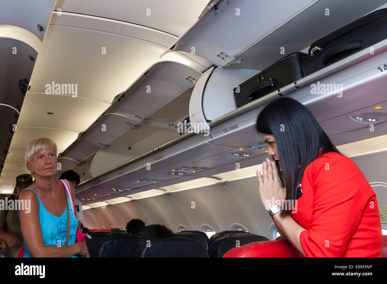 Air Asia flight attendant and passengers, on a flight from Phnom Penh, Cambodia to Bangkok, Thailand - Stock Image