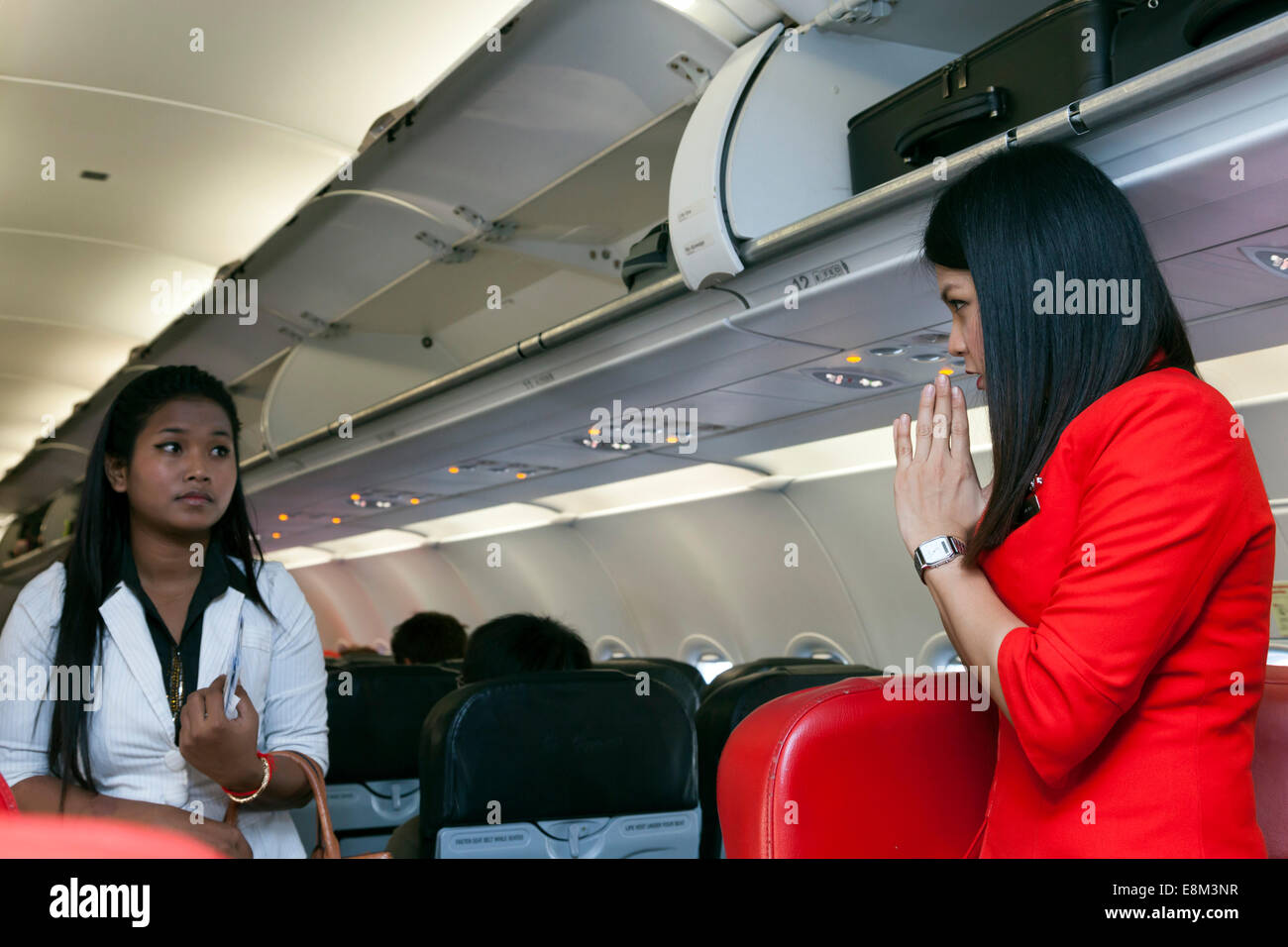 Air Asia flight attendant and boarding passenger - Stock Image