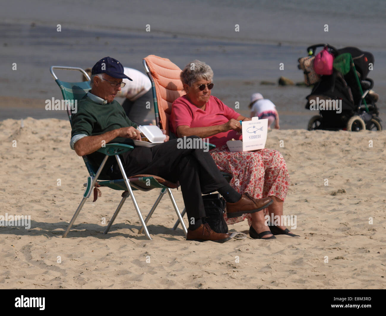 Pensioners eating fish and chips on the beach at Lyme Regis, Dorset, UK - Stock Image