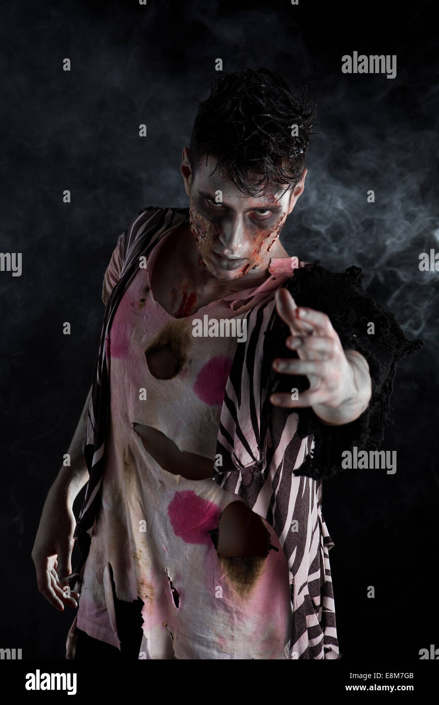 Male zombie standing on black smoky background, reaching hand towards camera - Stock Image