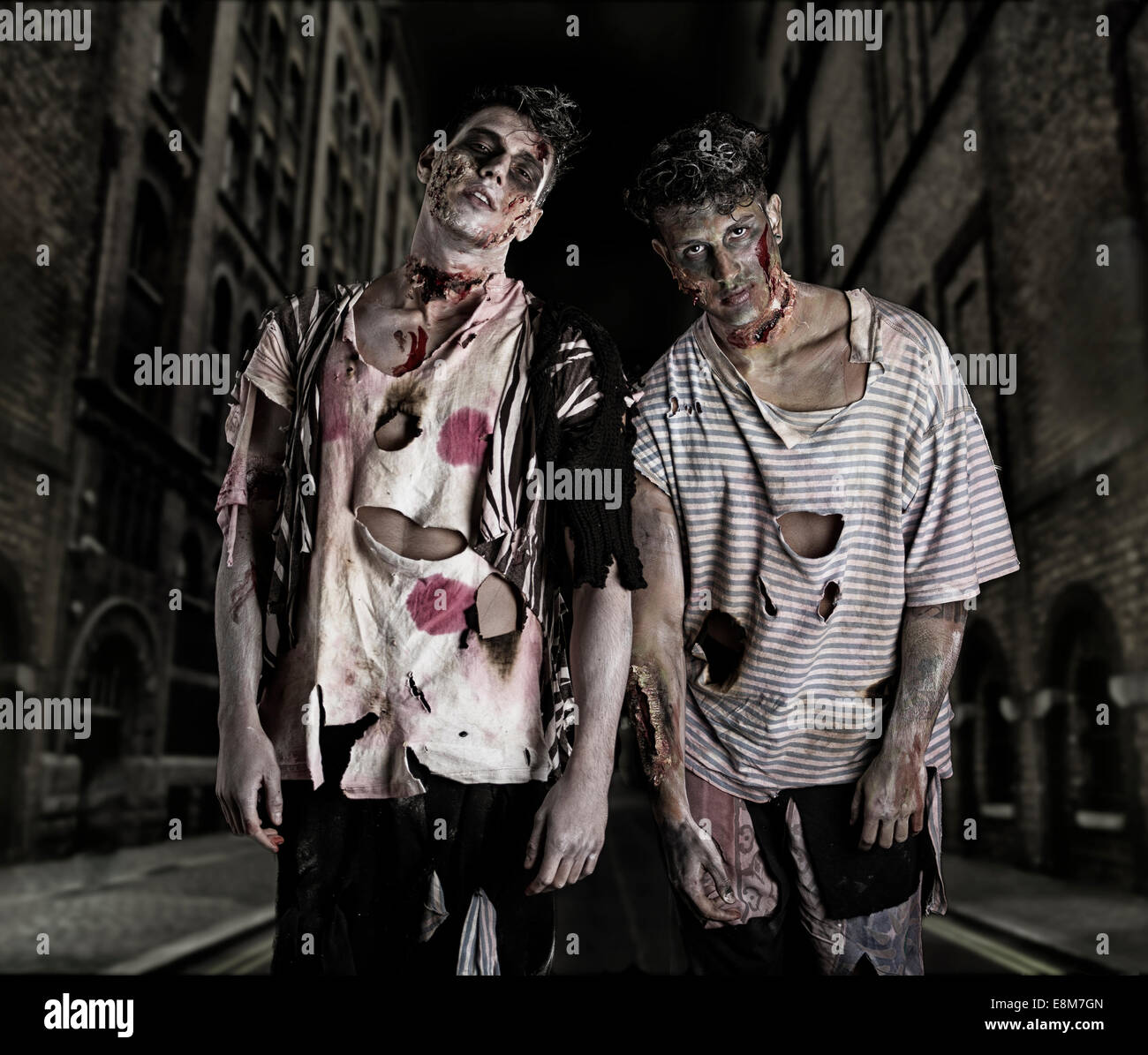 Two male zombies standing in empty city street at night looking at camera. Halloween theme - Stock Image