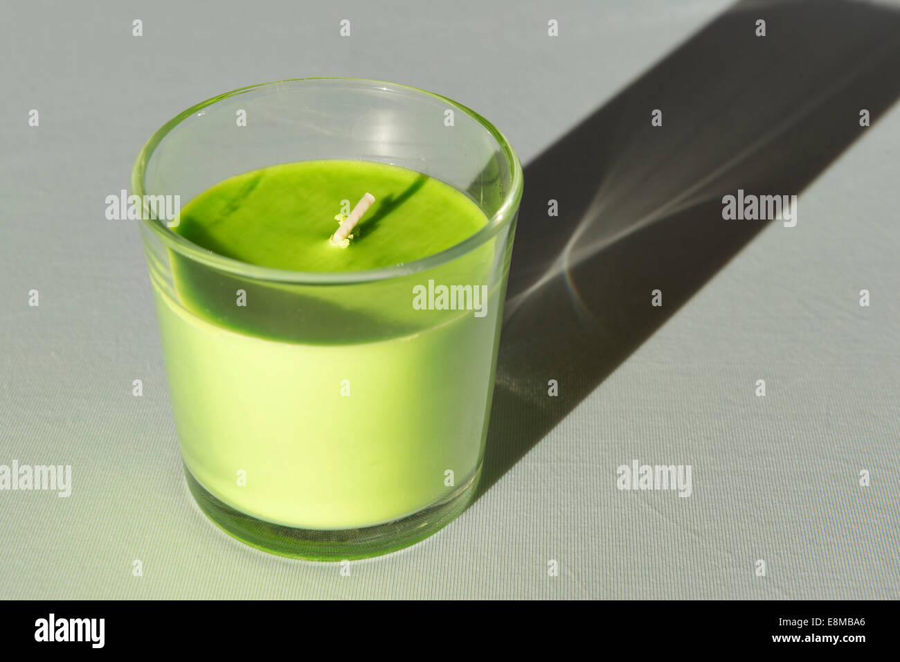 Image of a new green candle on a tablecloth in sunlight - Stock Image