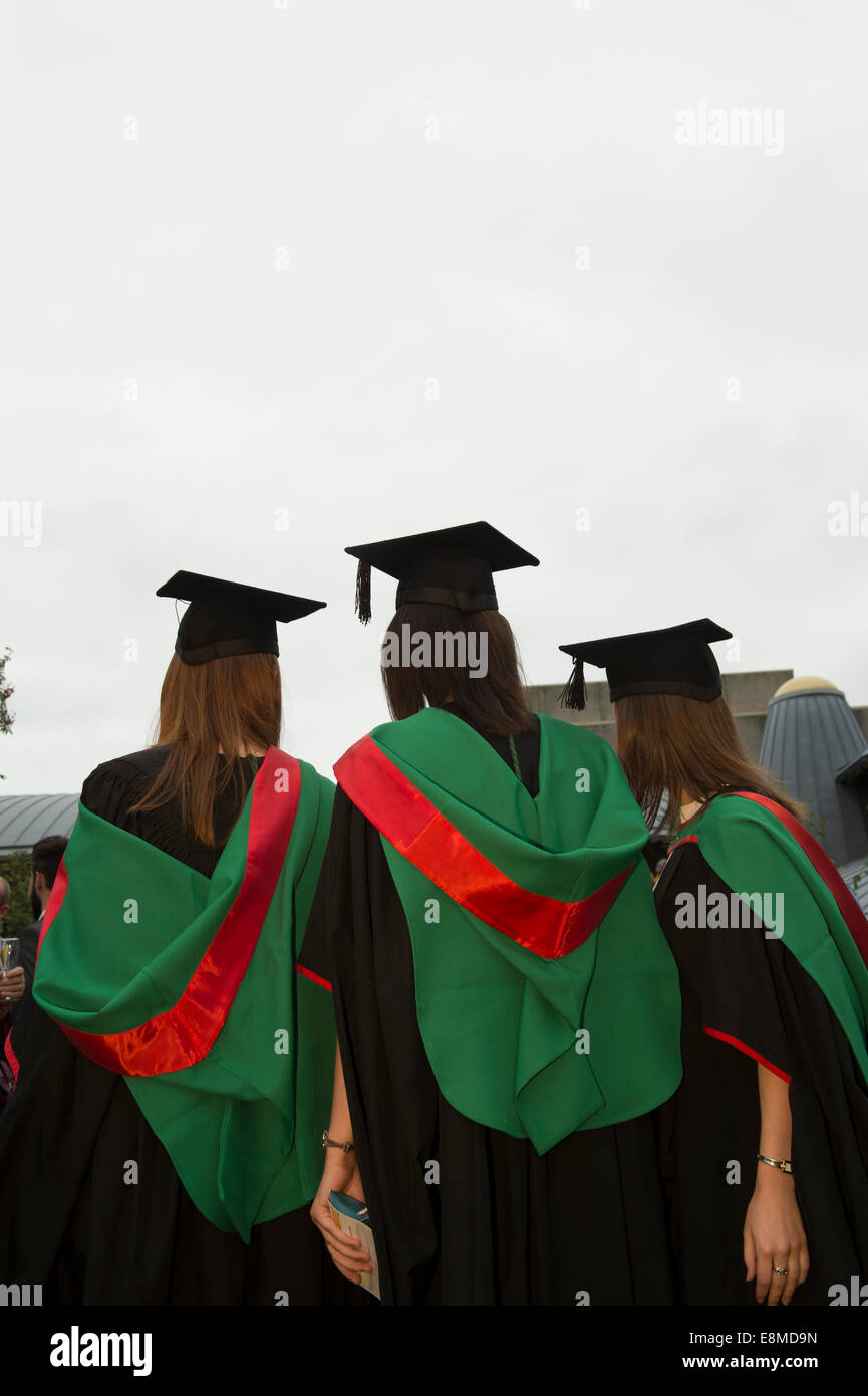 Three women students in their traditional gowns and mortar boards  graduating on graduation day Aberystwyth University, - Stock Image
