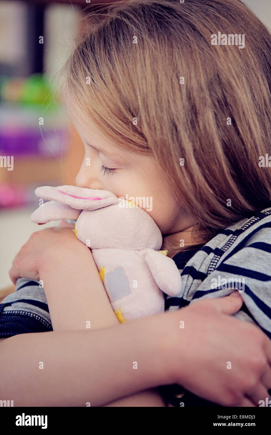 Young girl cuddling a stuffed toy comforter. Stock Photo