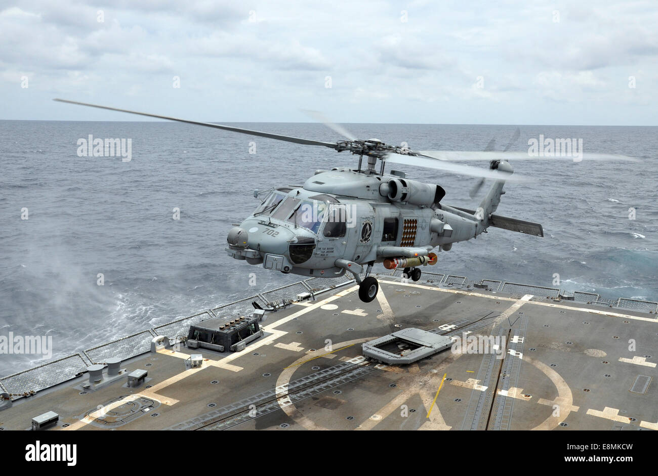 South China Sea, August 6, 2014 - An MH-60R Sea Hawk helicopter lifts off from the guided-missile destroyer USS - Stock Image