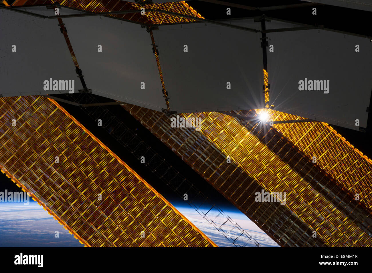 January 2, 2014 - The sun shines through a truss-based radiator panel and a primary solar array panel on the Earth - Stock Image