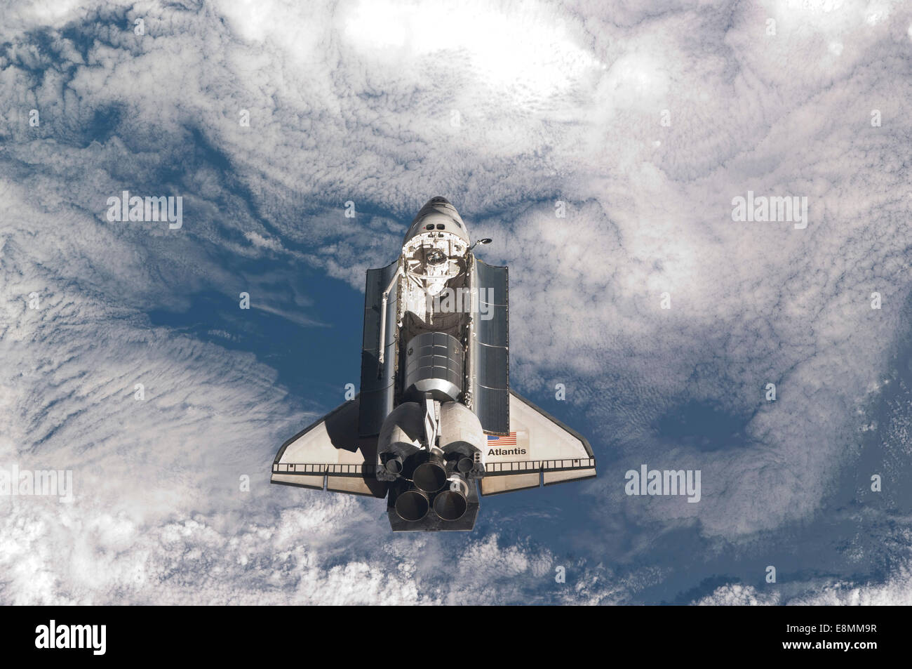 July 10, 2011 - Space shuttle Atlantis backdropped by a cloud covered Earth. - Stock Image