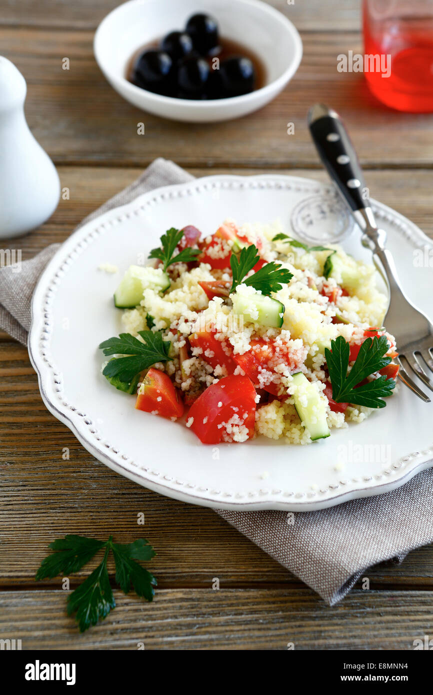 Salad with cooked couscous and vegetables on a white plate, nutritious food - Stock Image