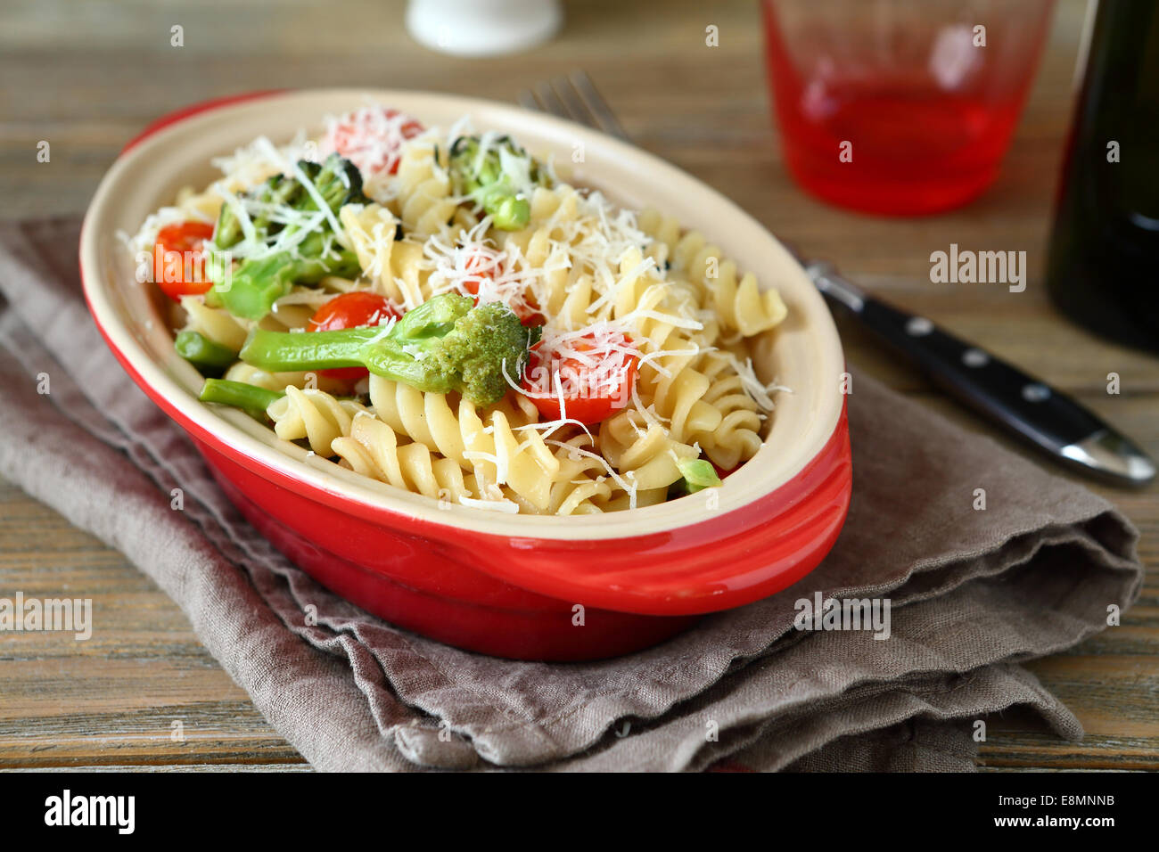 Pasta with grilled broccoli, shredded cheese and tomatoes, delicious italian food - Stock Image