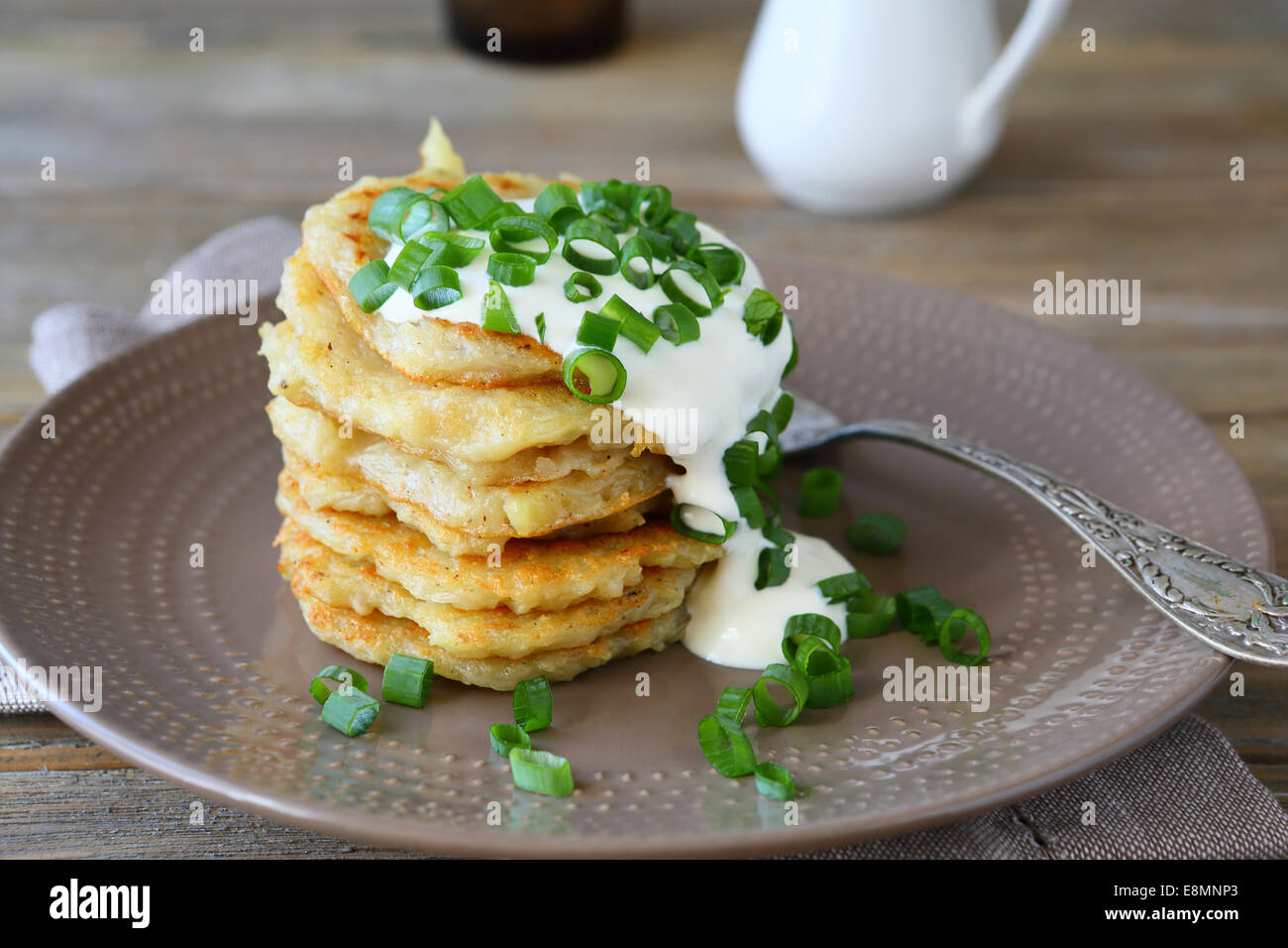 Potato pancakes with sour cream and green onions, delicious food - Stock Image