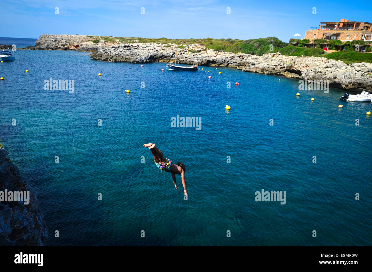 Cliff diving in the habour of the traditional small town of Binibequer Vell, on the Spanish island of Menorca, in - Stock Image