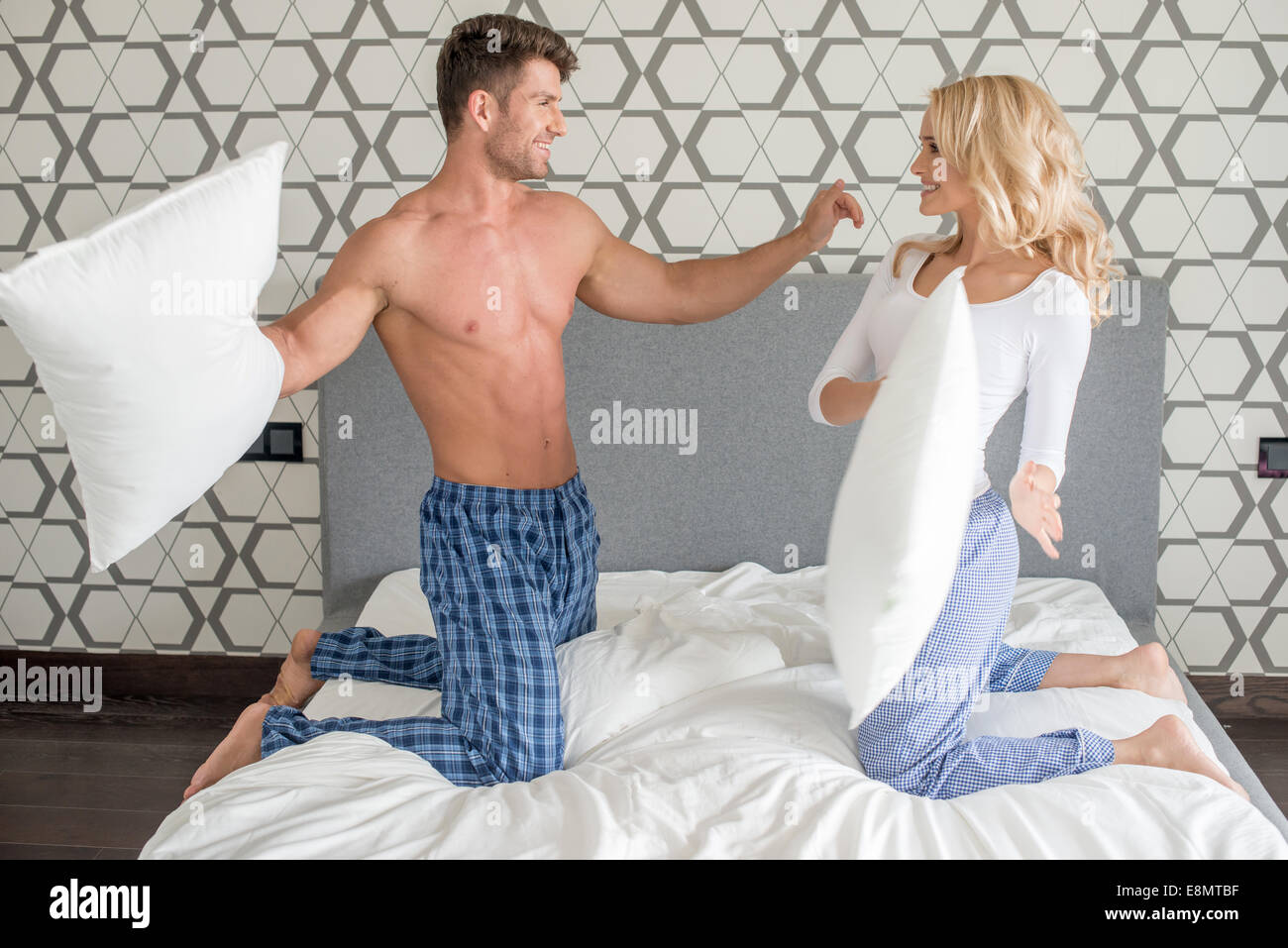 Couple in their sleepwear having a pillow fight - Stock Image