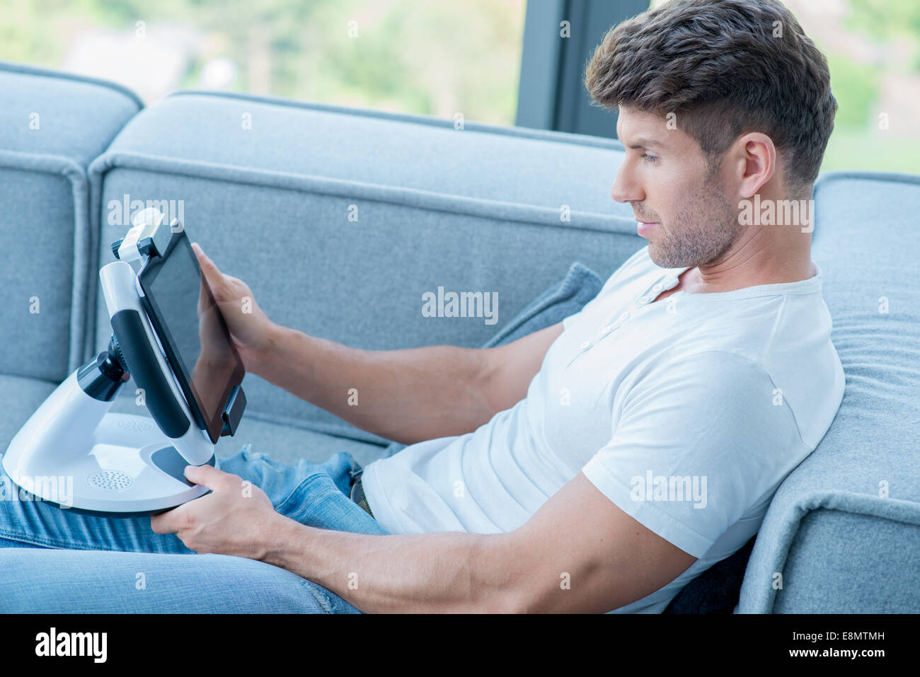 Young Handsome Man on Couch Playing His Gadget - Stock Image