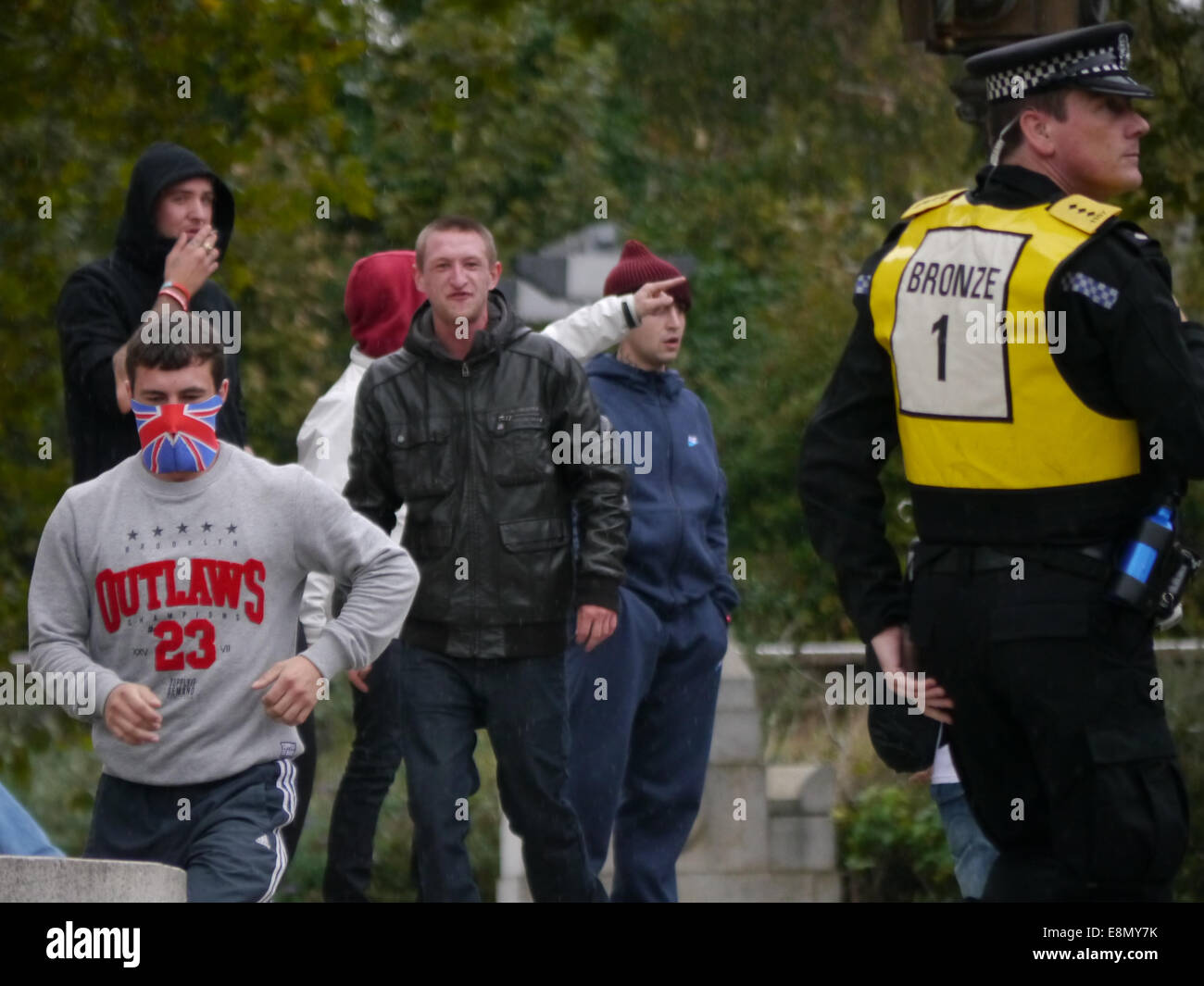 A member of the English Defence League, with his face covered leads a group of EDL members from the steps of Portsmouth - Stock Image