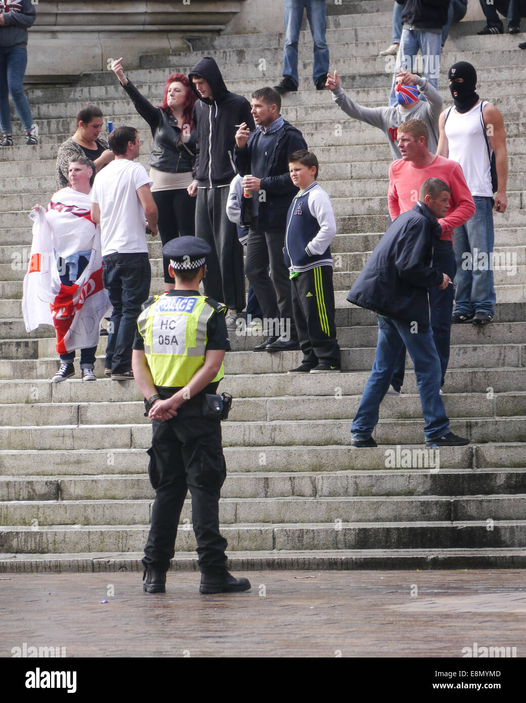 A Policeman stands in front of a group of young members of the English Defence League as they taunt anti fascist - Stock Image